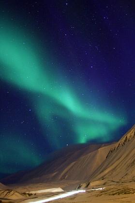 Zorza polarna nad lodowcem Longyear (Longyearbreen). Światła w dolnej części zdjęcia pochodzą od przejeżdżających skuterów śnieżnych. Fot. Jakub Małecki