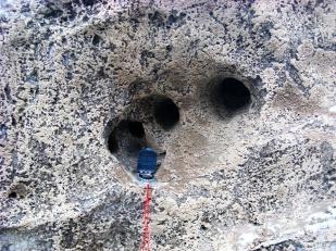 Woda wewnątrz lodowców tworzy systemy kanałów. Mogą one mieć bardzo różne rozmiary. Fotografia pokazuje trzy równoległe do siebie kanały w pionowej ścianie lodu lodowca Horbye o średnicy ok. 10 cm. Kompas dla skali. //Three parallel englacial channels ca. 10 cm wide, Horbye glacier (Horbyebreen). Fot. Jakub Małecki 2014//