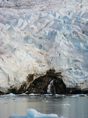Woda uchodzi z kanałów subglacjalnych na powierzchnię poprzez tzw. bramy lodowcowe. Zdjęcie pokazuje wypływ wód spod dużego lodowca Nordenskiold (w dolnej części fotografii). //Water outflow on Nordenskiold glacier (Nordenskioldbreen). Fot. Jakub Małecki, 2014//