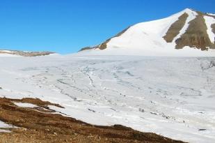 Sieć potoków supraglacjalnych na lodowcach przypomina sieć rzeczną w obszarach niezlodowaconych. W górnych częściach lodowców potoki są płytkie i niosą mało wody. Płynąc w dół łączą się ze sobą tworząc coraz większe koryta. Na fotografii przedstawiono sieć potoków supraglacjalnych w środkowej części lodowca Ebba. W górnej, płaskiej części lodowca zalega wciąż gruba pokrywa śnieżna pozbawiona jeszcze sieci odwadniającej. //Supraglacial drainage network on Ebba glacier (Ebbabreen). Fot. Jakub Małecki, 2008//