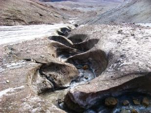 Kanały supraglacjalne cechują się niezwykłą krętością. Są tym głębsze, im więcej wody płynie kanałem i im bardziej stroma powierzchnia lodowca. To dlatego kanały są najgłębsze w częściach czołowych lodowców. Na zdjęciu: meandrujący potok supraglacjalny w części czołowej lodowca Ebba. //Supraglacial channel on Ebba glacier (Ebbabreen). Fot. Jakub Małecki, 2014//